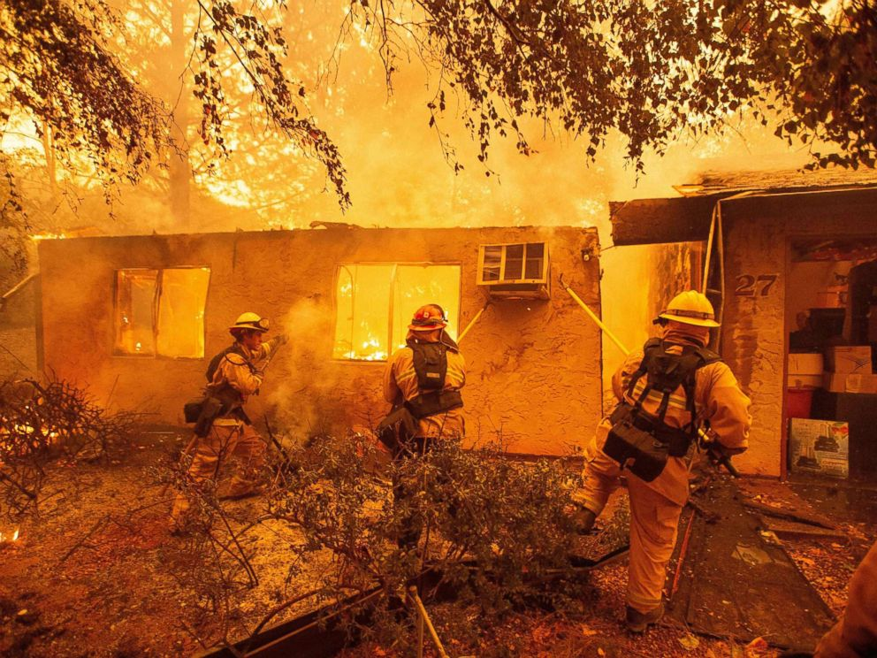 PHOTO: Firefighters push down a wall while battling a fire in an apartment complex in Paradise, Calif., Nov. 09, 2018.